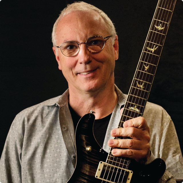 Paul Reed Smith in front of a black background holding out a guitar